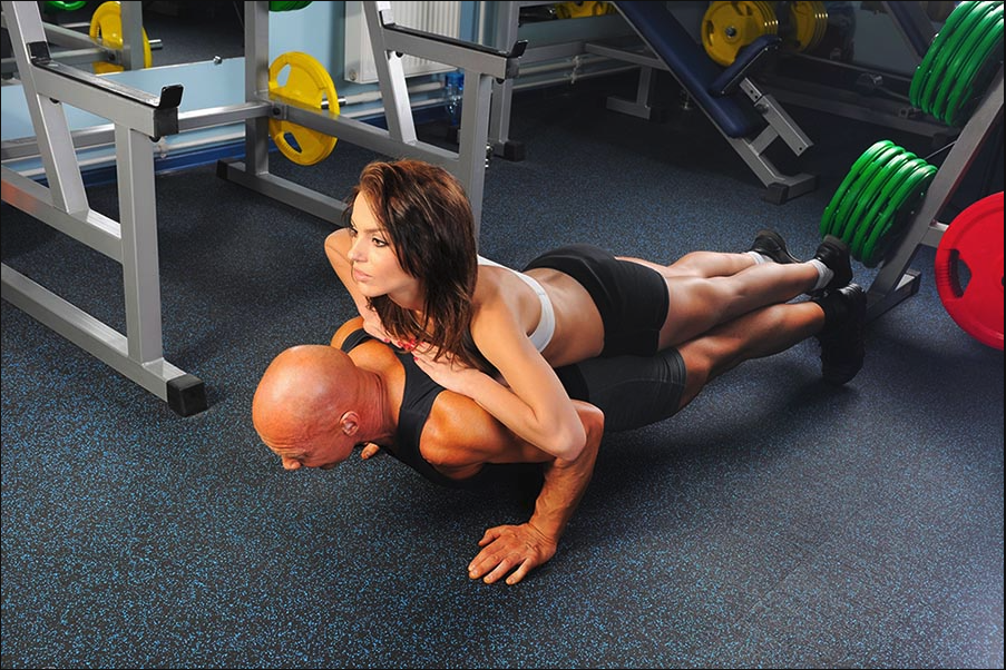 Man bench pressing woman's weight
